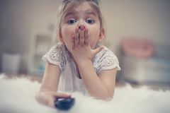 Cute little girl lying on floor. Shocked little girl watching TV lying on floor with remote control in hand Stock Photos