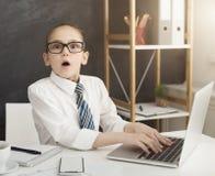 Shocked little girl working on laptop stock photo