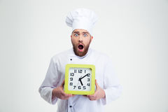 Shocked male chef cook holding wall clock Royalty Free Stock Photos