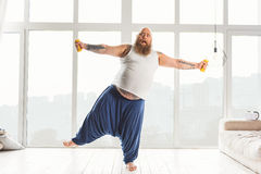 Shocked male fatso training with weights Royalty Free Stock Images