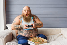 Shocked male heavy eater playing console. Excited fat man is entertaining with PlayStation at home. He is touching joystick and looking at camera with shock. His Stock Photo