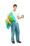Shocked male holding a pillow and alarm clock Royalty Free Stock Image