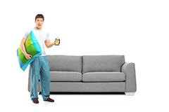 Shocked male in pajamas holding a pillow and alarm clock Stock Photo