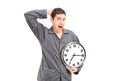 Shocked male in pijamas holding an alarm clock Royalty Free Stock Images