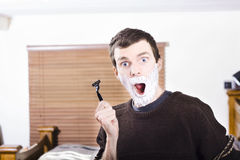 Shocked male with shaving cream and razor blade Stock Image