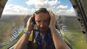 Shocked man in aerobatic aircraft in the sky stock footage
