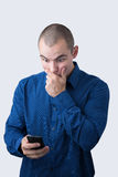 Shocked man browsing his smartphone Royalty Free Stock Photography