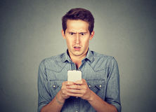 Shocked man checking mobile phone Stock Photography