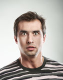 Shocked man. Close-up portrait of a shocked man looking at camera, studio shot, gray background Royalty Free Stock Images