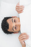 Shocked man covering face with sheet in bed Stock Image