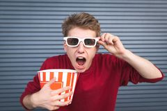 Shocked man with a cup of popcorn in his hands and 3D eyeglasses in his eyes, looking camera with astonished look. Shocked young man with a cup of popcorn in his stock images