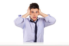 Shocked man in disbelief sitting at a table. Isolated on white background Royalty Free Stock Photo