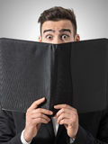 Shocked man expressive eyes reading restaurant menu prices. Stock Photography