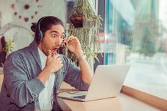 Shocked man in headphones looking surprised at laptop stock photography