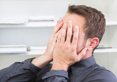 Shocked man hide face at office. Shocked confused man hide face with hands Royalty Free Stock Photos