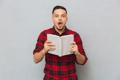 Shocked man holding book in hands. Shocked man in red shirt holding book in hands and looking at the camera over gray background Royalty Free Stock Image