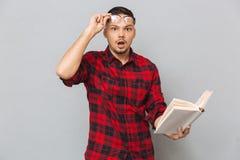 Shocked man holding book Stock Photo