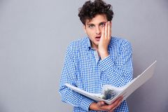 Shocked man holding folder of documents. Shocked young man standing with folder of documents and looking at camera royalty free stock photography