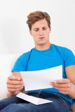 Shocked man holding paper. Tensed Young Man With Hand On Forehead Looking At Paper Stock Images