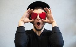 Shocked man holding red hearts on his eyes. Dressed in black, with hat. Valentines day background.