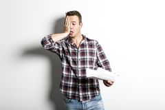 Shocked man holding some documents,  on gray background. A Shocked man holding some documents,  on gray background Royalty Free Stock Photo