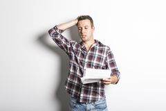 Shocked man holding some documents, isolated on gray background. A Shocked man holding some documents, isolated on gray background Stock Photo