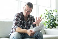 Shocked man holding some documents on sofa livingroom. A Shocked man holding some documents in the livingroom Stock Photo