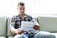 Shocked man holding some documents on sofa livingroom. A Shocked man holding some documents in the livingroom Royalty Free Stock Images