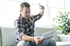 Shocked man holding some documents on sofa livingroom. A Shocked man holding some documents in the livingroom Royalty Free Stock Photos