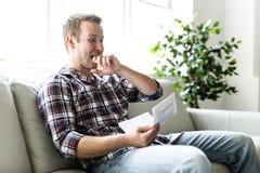 Shocked man holding some documents on sofa livingroom. A Shocked man holding some documents in the livingroom Royalty Free Stock Photo