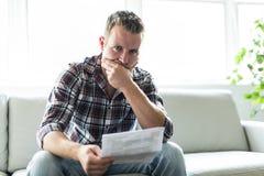Shocked man holding some documents on sofa livingroom. A Shocked man holding some documents in the livingroom Stock Images