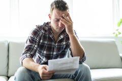 Shocked man holding some documents on sofa livingroom. A Shocked man holding some documents in the livingroom Stock Image