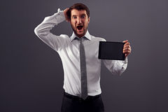 Shocked man holding tablet pc and screaming Stock Images