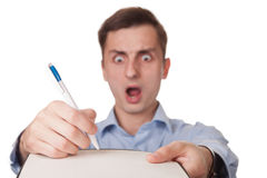 Horrified man signing document. Horrified young businessman signing blank document or bill, white background Royalty Free Stock Images