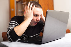 Shocked man with laptop Stock Images
