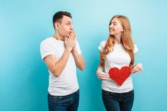Shocked man, learns about the pregnancy of his wife, a pregnant woman holding a red paper heart against the belly stock image