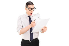 Shocked man looking at document through magnifier Royalty Free Stock Images