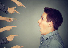 Shocked man looking at many fingers pointing at him Stock Image