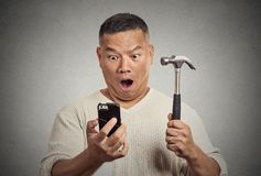 Shocked man looking at smart phone holding hammer Royalty Free Stock Images