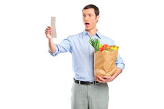 Shocked man looking at store receipt Royalty Free Stock Photos