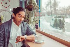 Shocked man looking to wristwatch for time, being late royalty free stock image