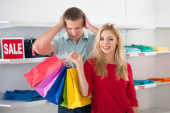 Shocked Man Looking At Woman Carrying Shopping Bags Stock Image