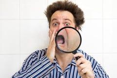 Shocked man in pajamas. Frightened man in pajamas watching his face magnifying glass royalty free stock image