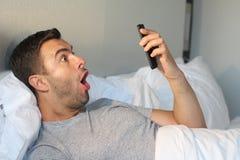 Shocked man reading something on cellphone.  stock photo