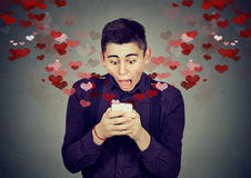 Shocked man receiving love sms text message on mobile phone Stock Image