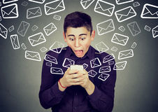 Shocked man receiving messages from smartphone email icons flying away Stock Images