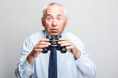 Shocked man. Searching with binoculars and looking surprised Stock Photography
