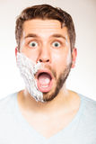 Shocked man with shaving cream foam on half face. Stock Images