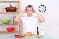 Shocked man sitting in the kitchen Stock Photography