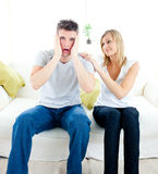 Shocked man sitting on sofa with his girlfriend Stock Photos